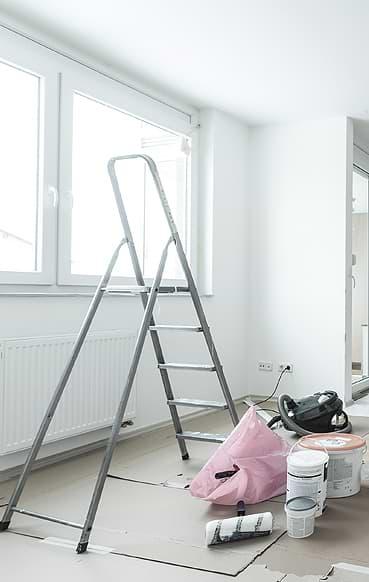 Renovierungsarbeiten in einer Privatwohnung – zu sehen ist eine Klappleiter, eine Farbrolle, verschiedene Farbeimer als auch ein Staubsauger. Der Fußboden ist bereits mit Pappe ausgelegt, um Farbspritzer zu vermeiden.